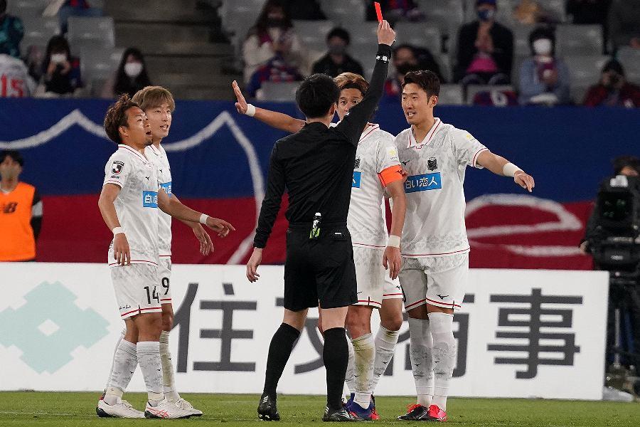 VARの介入により札幌DFキム・ミンテ(右端)はレッドカードに判定が変更された【写真:Getty Images】